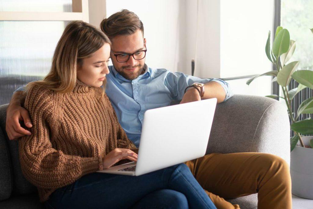 Par vid dator som söker lån med betalningsanmärkning